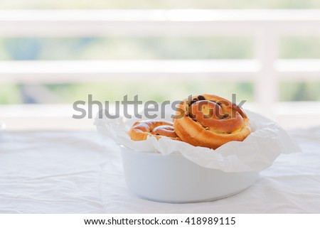Fresh baked vanilla sweet sugar buns with chocolate drops in a bowl on a wooden background with place for text, horizontal - stock photo