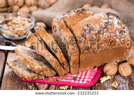 Fresh baked Walnut Bread (close-up shot) on wooden background
