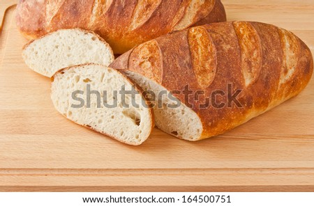 Fresh baked white bread on cutting board - stock photo