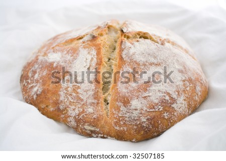 Fresh-baked white wheat bread on white cotton cloth - stock photo