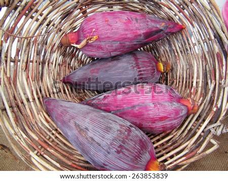 Fresh banana flower bud in the cane basket. - stock photo