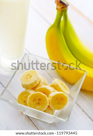 Fresh banana in the glass bowl, banana and milk - stock photo