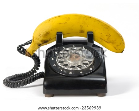 Fresh banana on retro phone. Isolated on white.