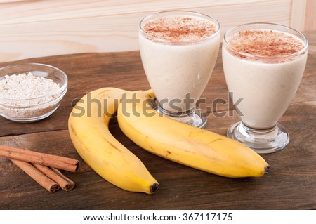 Fresh banana smoothie with oatmeal and cinnamon on wooden background - stock photo