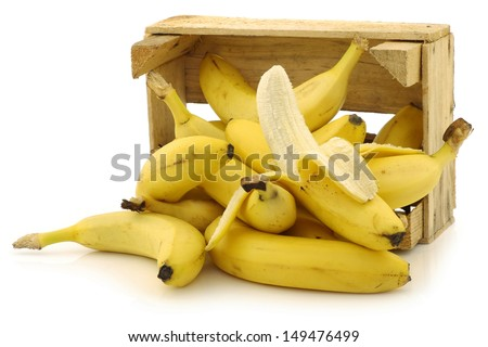 fresh bananas and a peeled one in a wooden crate on a white background - stock photo