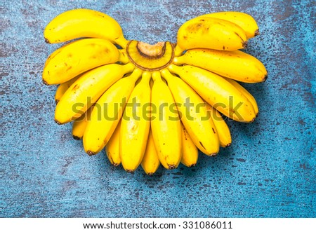 Fresh bananas on wooden background - Bananas on a wooden picnic  - stock photo