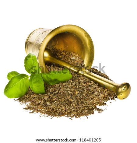 fresh basil and dried basil heaped next to a fallen bronze mortar and pestle isolated on white background - stock photo