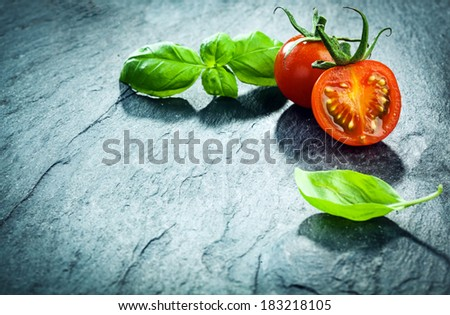 Fresh basil and grape tomato border arranged in the top right corner of the frame on a textured cracked background with copyspace - stock photo