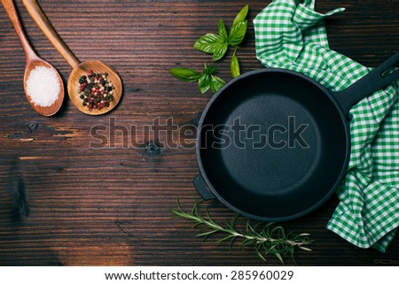 Fresh basil and rosemary, sea salt and dry peppercorns in wooden spoons near the frying pan - stock photo