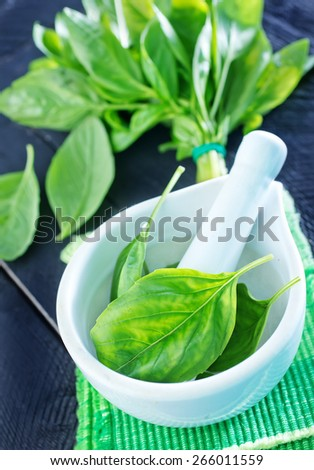 fresh basil in bowl and on a table - stock photo
