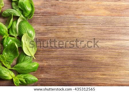 Fresh basil leaves on wooden background - stock photo