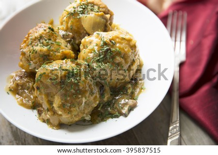 Fresh Bavarian bread dumplings with mushroom gravy sauce. - stock photo