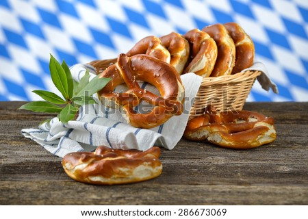 Fresh Bavarian pretzels in a breadbasket on a wooden table, in the background the white-blue flag of Bavaria - stock photo