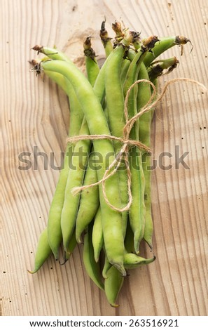 fresh beans broad over wood background, selective focus - stock photo