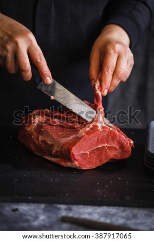 Fresh beef butcher meat. Farmer Hand holding eco meat of muscle meat beef ready to cook over black marble table.  - stock photo