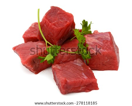 fresh beef cubes and cilantro on white background  - stock photo