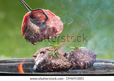 Fresh beef steaks on grill, barbecue on garden. - stock photo