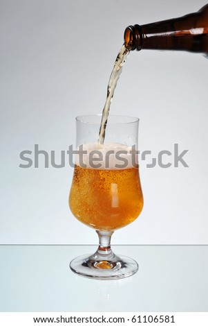 Fresh beer filling glass on stem, transparent decorative tankard. Part of brown dark bottle of alcohol beer and pouring liquid to mug making plenty bubbles of air in beer and foam. Object on glass - stock photo