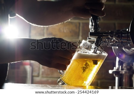 Fresh beer filling up the glass with beautiful lens flare from the back. - stock photo