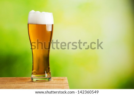 Fresh beer glass on natural background - stock photo