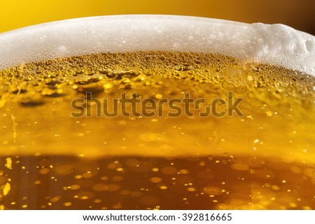 Fresh beer in glass with foam close up NOTE focus is located on the foam top right - stock photo