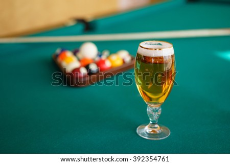 Fresh beer on a pool table. A glass of cold beer on a pool table. - stock photo