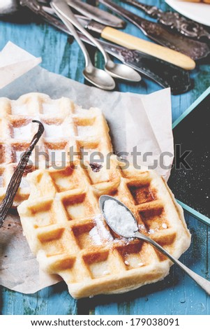 Fresh belgian waffles served with powdered sugar and vintage cutlery over blue wooden table. See series - stock photo