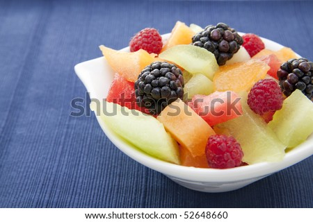 Fresh berries and diced melon in an ornate white bowl on a blue placemat. - stock photo