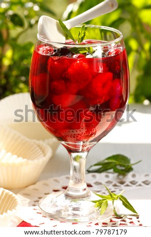 Fresh berries in a jelly with leaf of mint and spoon.