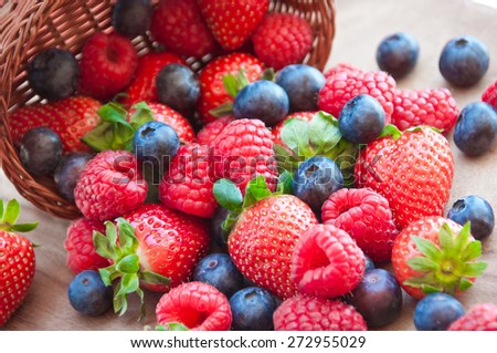 Fresh berries in basket - stock photo