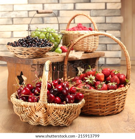 Fresh berries in basket on wall background - stock photo