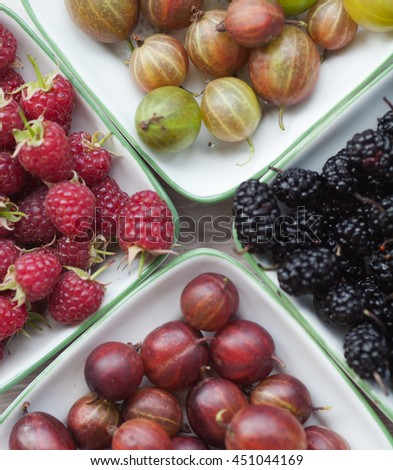 Fresh berries on a board and wooden table. Fresh raspberries, gooseberry,  mulberries. Decorated with leaves. Horizontal image. Top view. View from above - stock photo