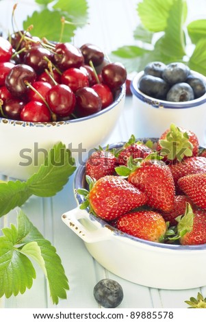 Fresh berries on blue background - stock photo