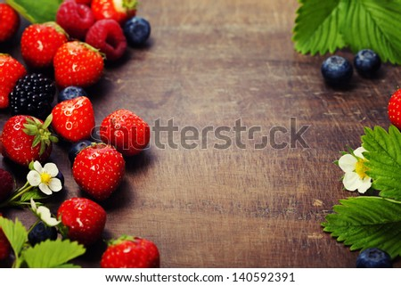 fresh berries on wooden background - stock photo