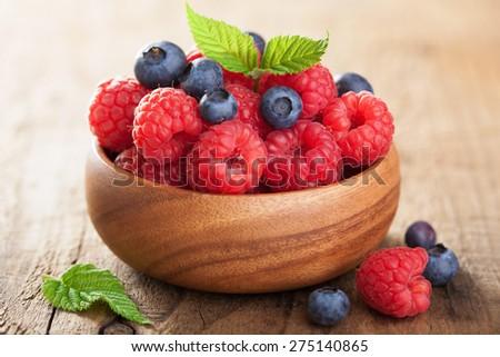 fresh berries raspberry blueberry in wooden bowl - stock photo
