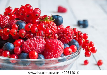 Fresh berries (raspberry, red currant, blueberry) in glass bowl on wooden table  - stock photo