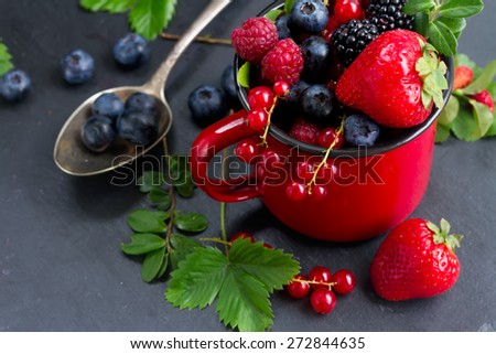 fresh  berries with green  leaves   on black stone background - stock photo