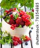 fresh berries with leaves in a wooden basket - stock photo
