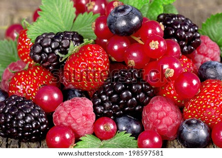 Fresh berries with mint leaves on a wooden background - stock photo