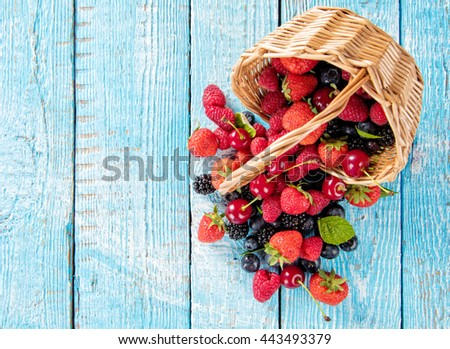 Fresh berry fruit pile in basket with leaves placed on old wooden planks. Shot from aerial view, copyspace for text - stock photo