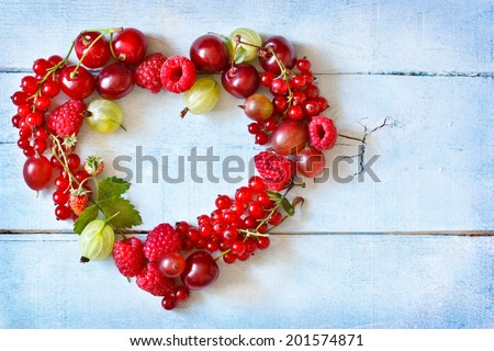 Fresh berry heart shape frame on an old wooden background. - stock photo