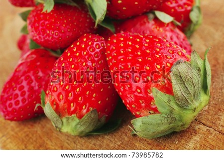 fresh berry: ripe raw strawberry over wooden plate