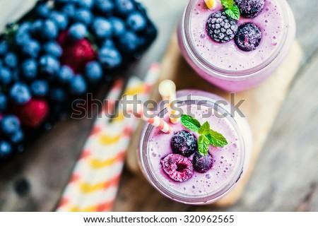 Fresh berry smoothies on mason jars - stock photo