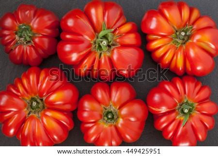 Fresh big Heirloom tomatoes on black background, flat lay. - stock photo