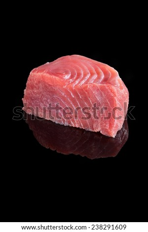 Fresh big tuna steak isolated on black background. Sashimi sushi, seafood eating, healthy food. - stock photo