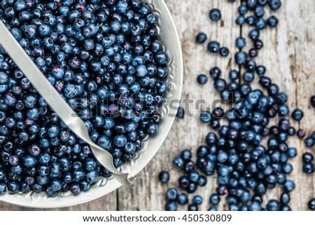 Fresh bilberries in basket, ripe berries from forest on wooden table, top view - stock photo