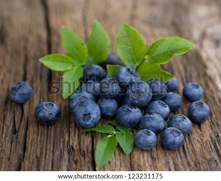 Fresh bilberries on wooden ground - stock photo