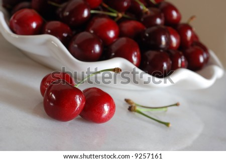 Fresh bing cherries reflecting on a shiny marble table with decorative bowl of cherries in the background.  Tilted composition with extremely shallow dof.  Main focus on the front cherry. - stock photo
