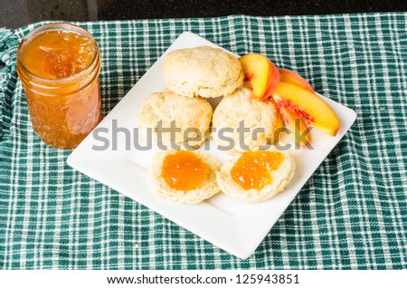 Fresh biscuits with homemade peach jam on white plate - stock photo