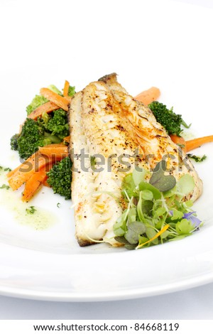 Fresh black cod on bed of broccoli and carrots with a touch of micro herbs